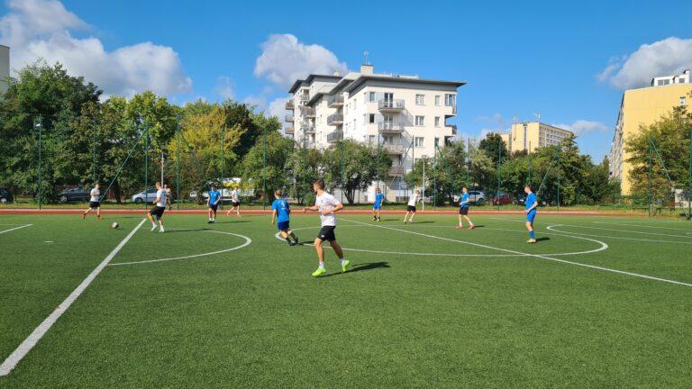 Zawodnicy grający w piłkę nożną na boisku zewnętrznym.
