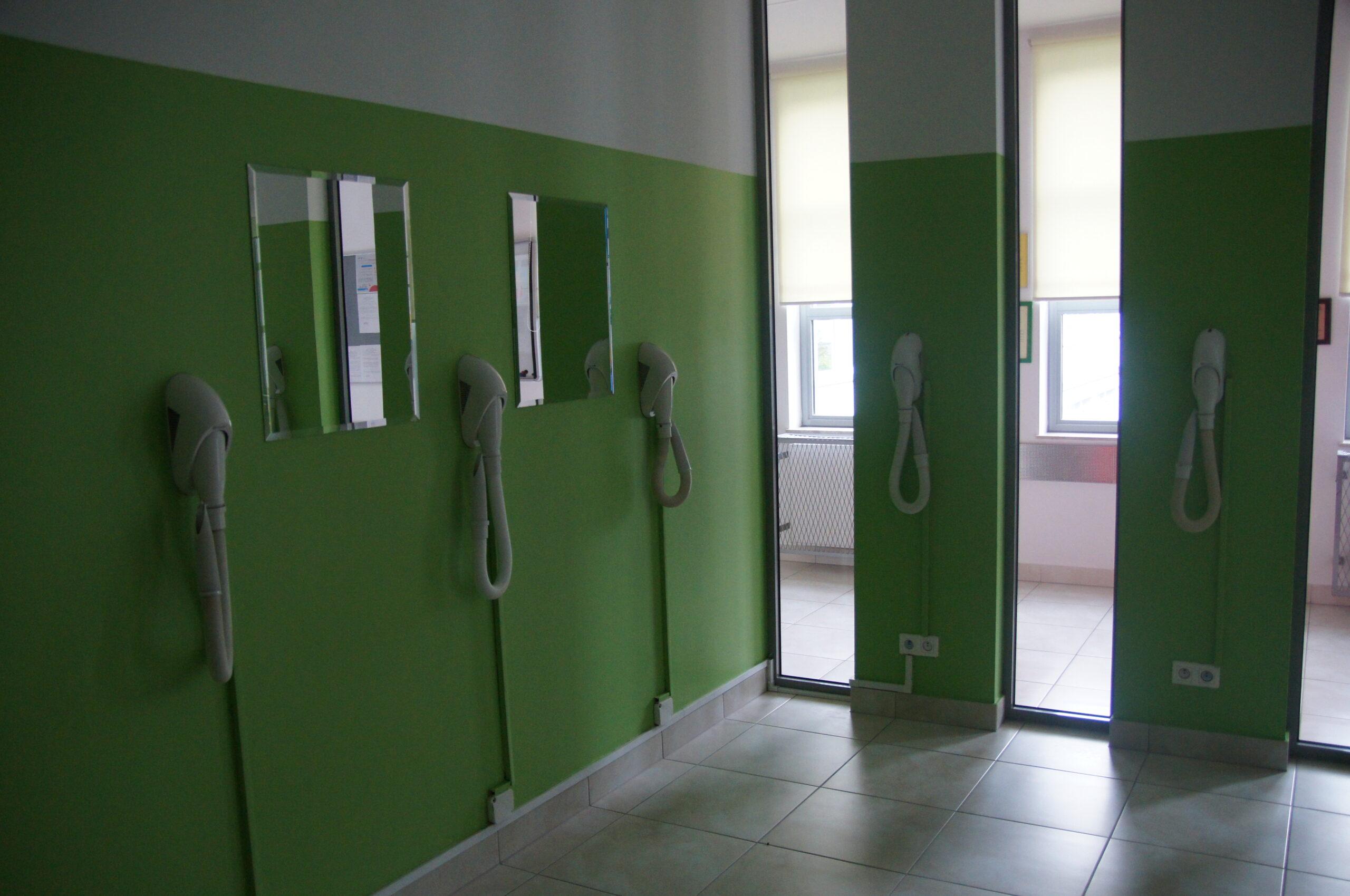 Suszarki na tle zielonej ściany.